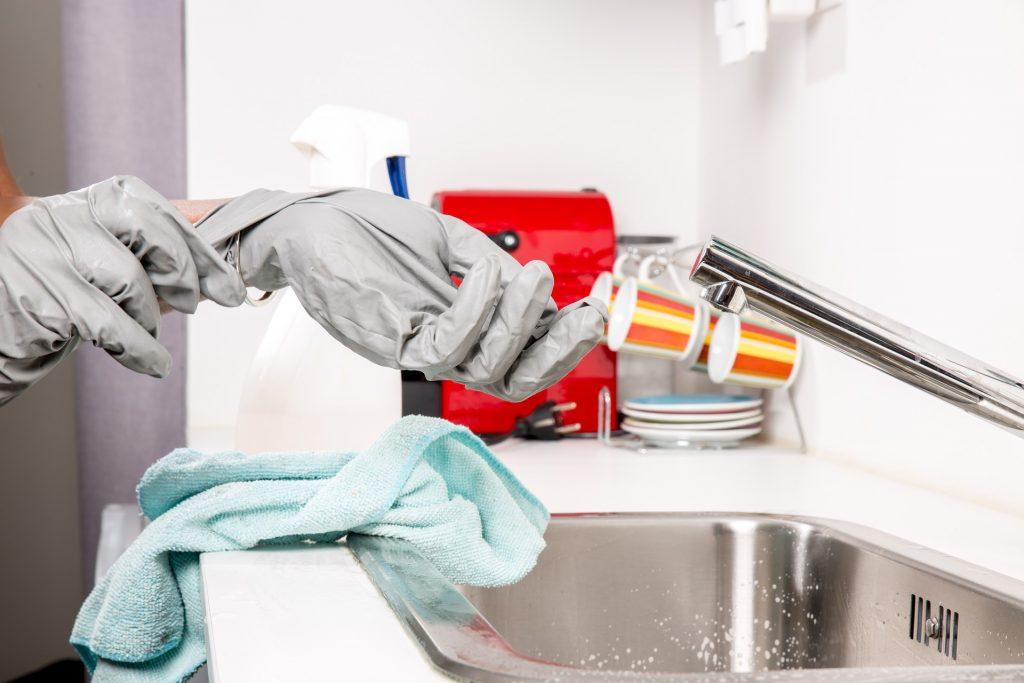 Person zieht Gummihandschuhe am Waschbecken aus