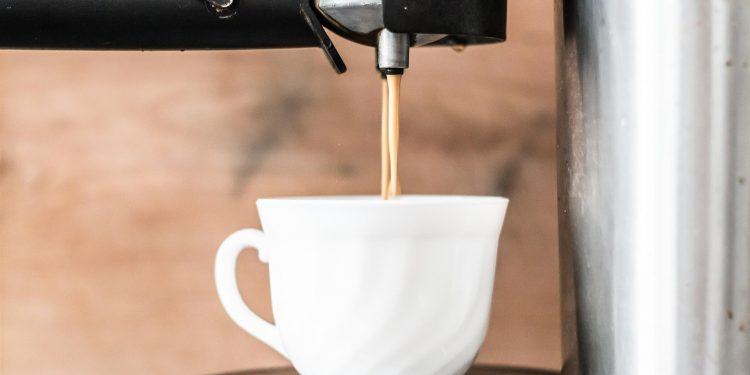 Frisch gebrühter Kaffee läuft von der Maschine in die Tasse